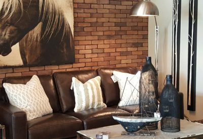 Masculine living area featuring dark leather and nautical accessories in the Embellish My Home showroom.